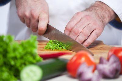 Schnitttechnik von Aramark Koch: Gemüse mit Messer schneidenmit dem Messer zeigt