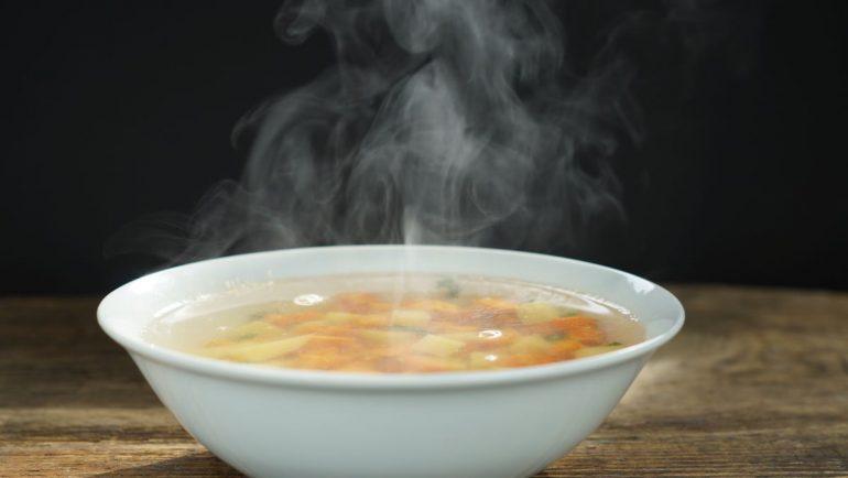 Suppemschüssel mit dampfender Hühnersuppe